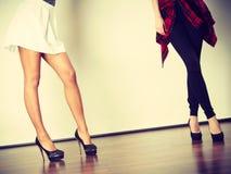 Two women legs presenting high heels Stock Photos