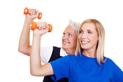 Two women lifting dumbbells Stock Photos