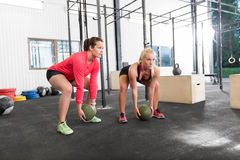 Two women lifts crossfit slam balls Stock Photos