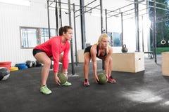 Two women lifts crossfit slam balls. Young women lift slam balls at crossfit gym center stock photos