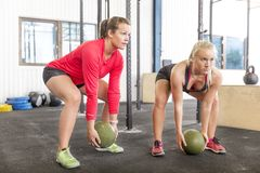 Two women lifts crossfit slam balls Stock Images