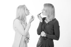 Two women with lipsticks Stock Photography