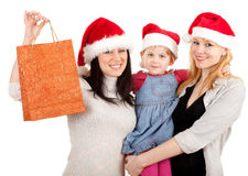 Two women and little girl in Santa hat Stock Photo