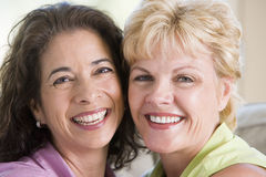 Two women in living room smiling Stock Photos