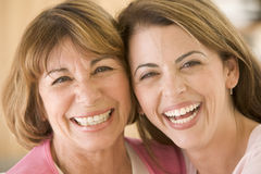 Two women in living room smiling. Close up of two women in living room smiling Royalty Free Stock Photo