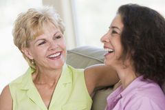 Two women in living room talking and smiling stock photography