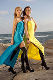Two women in long dresses on the beach Stock Image