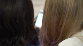 Two women look in the smartphone. A type of two heads of girls behind looking in phone. Two girls look in the smartphone. On this video you can see as the woman stock video