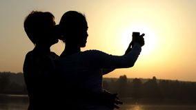 Two women look at their mobile phone on a lake bank in slo-mo. An original view of two women looking at their mobile phone videos on a picturesque lake bank at stock footage