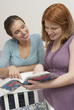 Two Women Looking At Book By Cradle Stock Photography