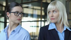 Two women looking different sides, competing at work, blond and brunette rivalry