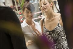 Two women looking at a display window of a store. Royalty Free Stock Photo