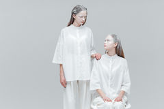 Two women looking at each other in white clothes. Two beautiful fashion women looking at each other in white clothes over gray background Stock Photo