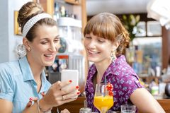 Two women looking at mobile phone royalty free stock image