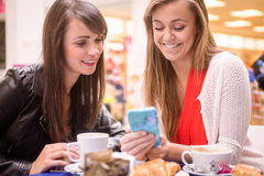 Two women looking at mobile phone while having snacks and coffee Royalty Free Stock Images