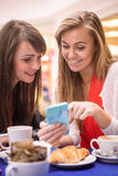 Two women looking at mobile phone while having snacks and coffee Royalty Free Stock Photo