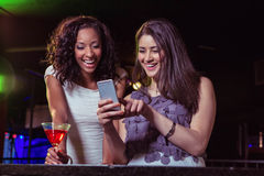 Two women looking at mobile phone and smiling at bar counter Royalty Free Stock Image
