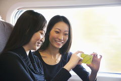 Two Women Looking At Mobile Phone on a Train Royalty Free Stock Photography