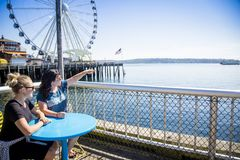 Two women looking out at the Seattle harbor on a sunny day Stock Images