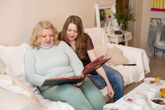 Two women looking photo album. Mother and daughter. Royalty Free Stock Photography