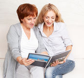 Two women looking photo book Royalty Free Stock Images