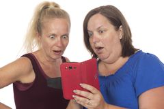Surfing the Web for Gossip and Controversy. Two women looking at a smart phone with expressions of surprise, amazement Stock Images
