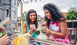 Two women looking smartphone and drinking green smoothies Stock Images