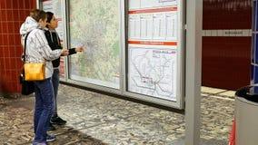 Two women looking at subway metro map. Hamburg, Germany - October, 10, 2016: Two women looking at subway metro underground tube map on train station. Tourists Stock Photos