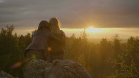 Two women are looking on the sunset. Two pretty women are sitting on the stone and looking on the sunset in the forest stock video