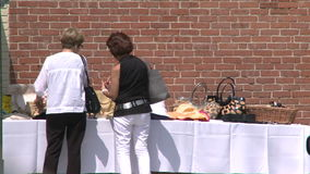 Two women looking at table at sidewalk sale. A view or scene from around town stock footage