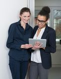 Two women are looking at a tablet Stock Images