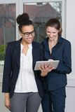 Two women are looking at a tablet Stock Image