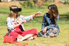 Two women looking in VR glasses and gesturing with his hands out Royalty Free Stock Images
