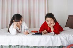 Two women lying on the bed Stock Photos