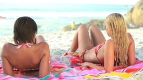 Two women lying down on their beach towels. While tanning stock video footage