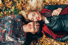 Two women lying in the leaves Royalty Free Stock Photos