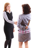 Two women make handshake on of them holds knife behind her back Stock Images