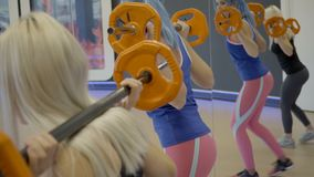 Two women make lunges with free weight in sports club. They stand with barbells on shoulders and take step backward synchronously, squatting to floor level stock video footage
