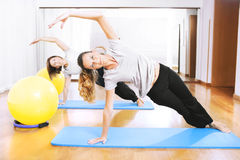 Two women making a fitness exercisen in synchrony. Two teachers making a fitness exercisen in synchrony Stock Photography