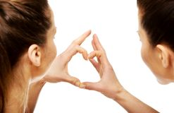 Two women making heart with fingers. Stock Photo