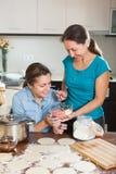 Two  women making  pies or  meat dumplings Stock Photos
