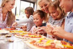 Two women making pizza with kids Royalty Free Stock Photo