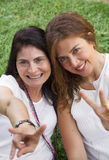 Two women making victory sign Stock Images