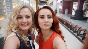 Two women at the mall take selfie. Two pretty women at the mall take selfie stock video