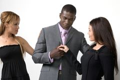 Two women and a man. A studio view of a handsome, well-dressed African American man and two beautiful multi racial women where the man seems to have the Stock Photo