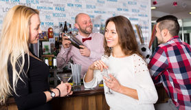 Two women and man in bar Stock Image