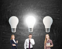 Two women and man and big light bulbs Stock Image