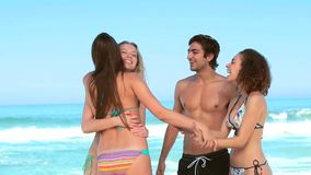 Two women and a man together at the beach. As another girl appears stock footage