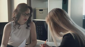 Two women manager and client sign some documents in office. Attractive woman with brown eyes, red full lips, dark curly long hair in white transparent blouse stock video footage