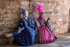 Two masked women sitting on a stone bench during Venice Carnival. Two women in masks and ornate blue and pink costumes and decorative fans, sitting on a stone stock photos